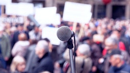 Microphone in focus against blurred protesters