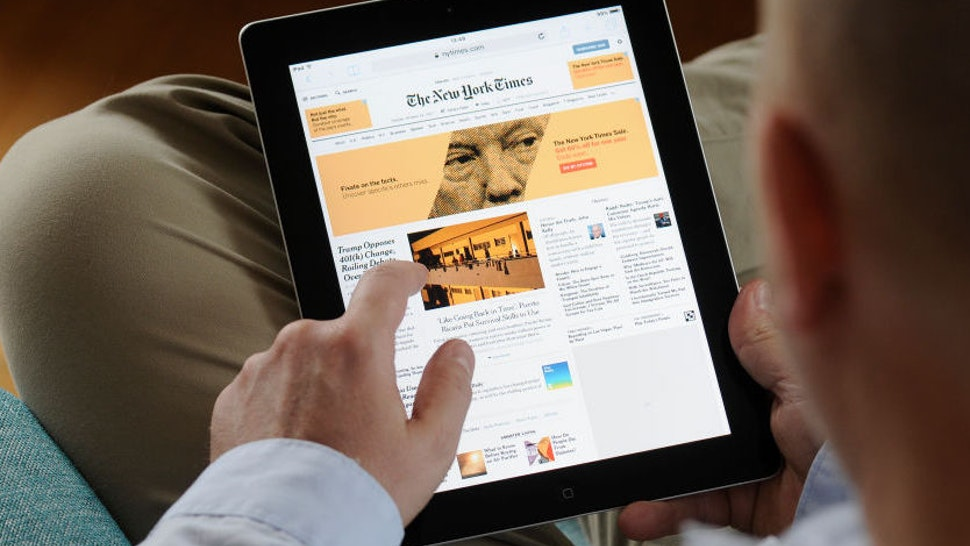 A man is seen reading the New York Times on an iPad on October 24, 2017.