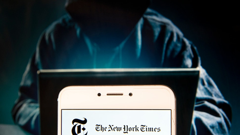 In this photo illustration, the American newspaper The New York Times logo is seen displayed on an Android mobile device with a figure of hacker in the background.