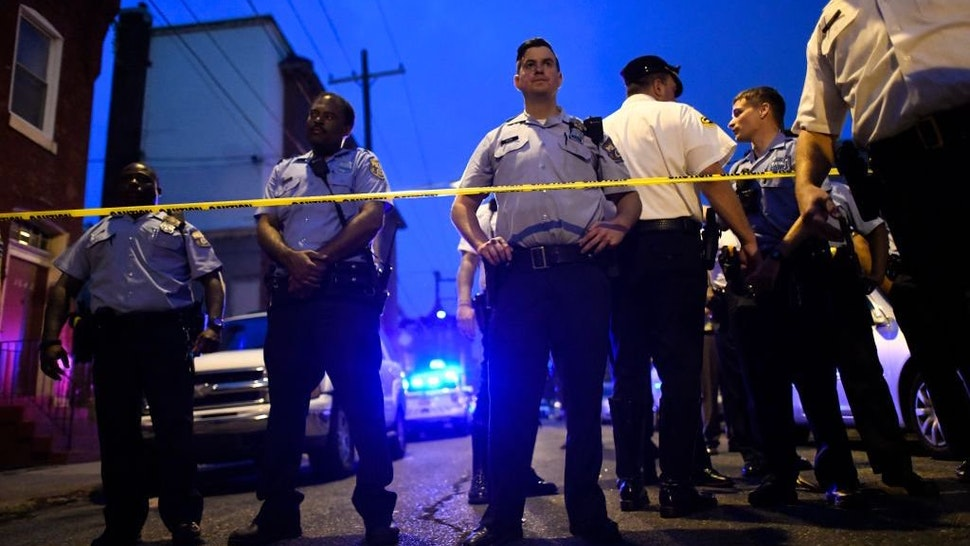 Police officers monitor activity near a residence while responding to a shooting on August 14, 2019 in Philadelphia, Pennsylvania.