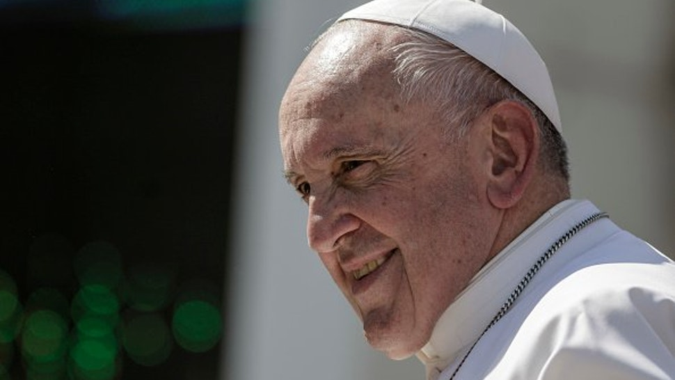 Pope Francis smiles as he leaves at the end of an audience with penitentiary police members in St. Peter's Square.