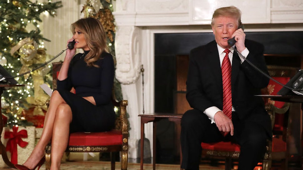 WASHINGTON, DC - DECEMBER 24: U.S. President Donald Trump (R) and first lady Melania Trump take phone calls from children as they participates in tracking Santa Claus' movements with the North American Aerospace Defense Command (NORAD) Santa Tracker on Christmas Eve in the East Room of the White House December 24, 2018 in Washington, DC. This is the 63rd straight year that NORAD has publicly tracked Santa's sleigh on its global rounds.