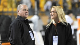 Radio talk show host and political commentator Rush Limbaugh (L) and his wife, Kathryn Rogers, look on from the sideline before a National Football League game between the New England Patriots and Pittsburgh Steelers at Heinz Field on November 14, 2010.