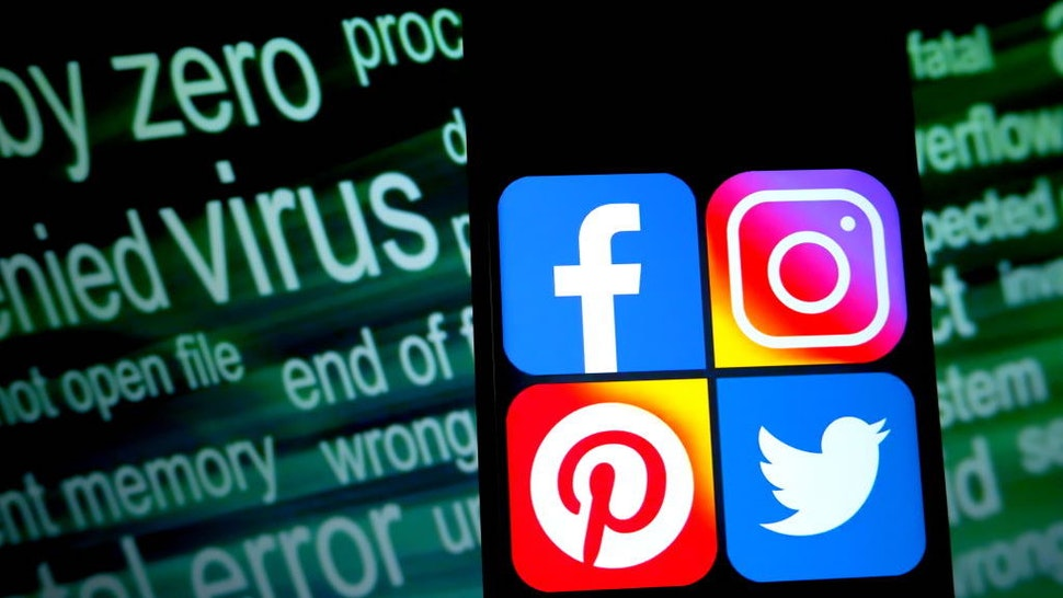 In this photo illustration online social media logos are seen displayed on a smartphone.