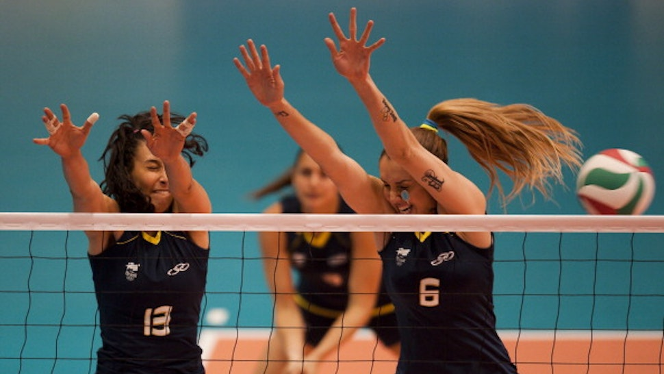 Sheila Castro (L) and Thaisa Menezes try to block the ball during the preliminary match against Canada at the Pan American Vollyeball complex