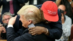 U.S. President Donald Trump hugs rapper Kanye West during a meeting in the Oval office of the White House on October 11, 2018 in Washington, DC.