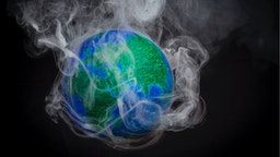 A picture taken on November 10, 2015 shows a small globe surrounded by smoke to illustrate global warming. France will be hosting and presiding the 21st Session of the Conference of the Parties to the United Nations Framework Convention on Climate Change (COP21/CMP11), also known as Paris 2015 from November 30 to December 11.