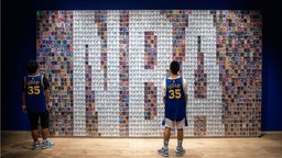 Two Chinese youths stand in front of a wall displaying basketball trading cards at the NBA exhibition in Beijing on August 19, 2019. - The Basketball world cup will be held from August 31 to September 15 2019 in China.