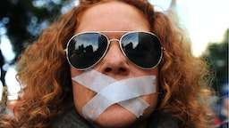 A woman wears tape over her mouth during a demonstration called by Nosomosdelito, a regrouping of some 40 collectives in Sevilla, against Spain's proposed new public security law, which introduces hefty fines for unauthorised protests and allows for the summary expulsion of migrants that try to enter the country illegally, has sparked fierce opposition from human rights activists, in Sevilla on December 27, 2014.