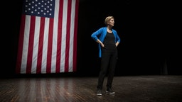 Senator Elizabeth Warren, a Democrat from Massachusetts and 2020 presidential candidate, stands on stage during a campaign event at Iowa State University in Ames, Iowa, U.S., on Monday, Oct. 21, 2019. Warrenunveiled an $800 billion plan to fund her progressive proposal for reshaping U.S. public education and disclosed that her signaturewealth taxwill pay for school and child-care initiatives -- in effect transferring the cost of raising a child from birth to college to America's richest families. Photographer: Daniel Acker/ Bloomberg