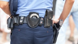 Midsection Rear View Of Police Man With Belt With Handcuffs And Gun - stock photo