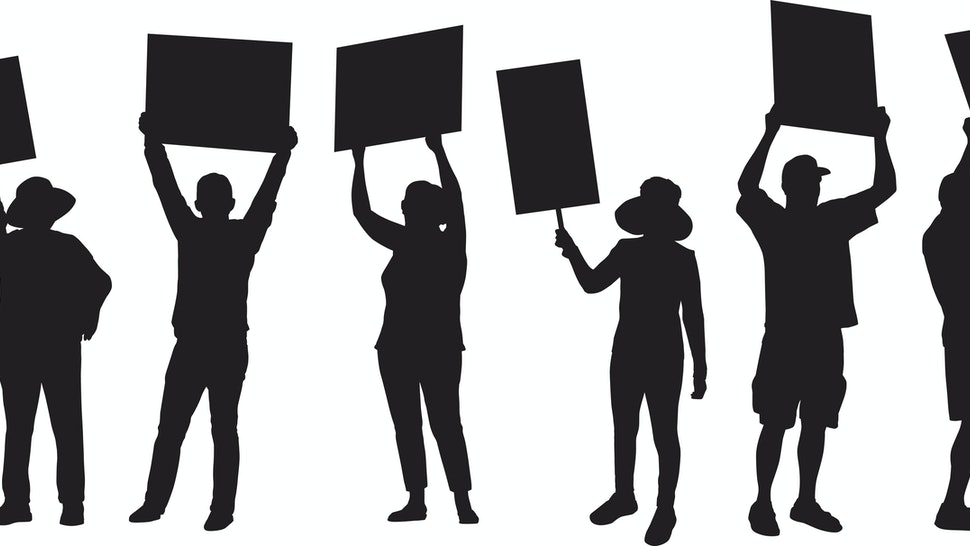 Vector silhouette of six standing people holding up protest signs.