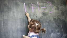 Two year old girl holding chalk pointing at a blackboard