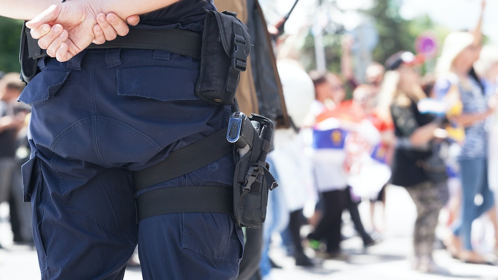 Midsection Of Police Force Against Crowd During Protest - stock photo