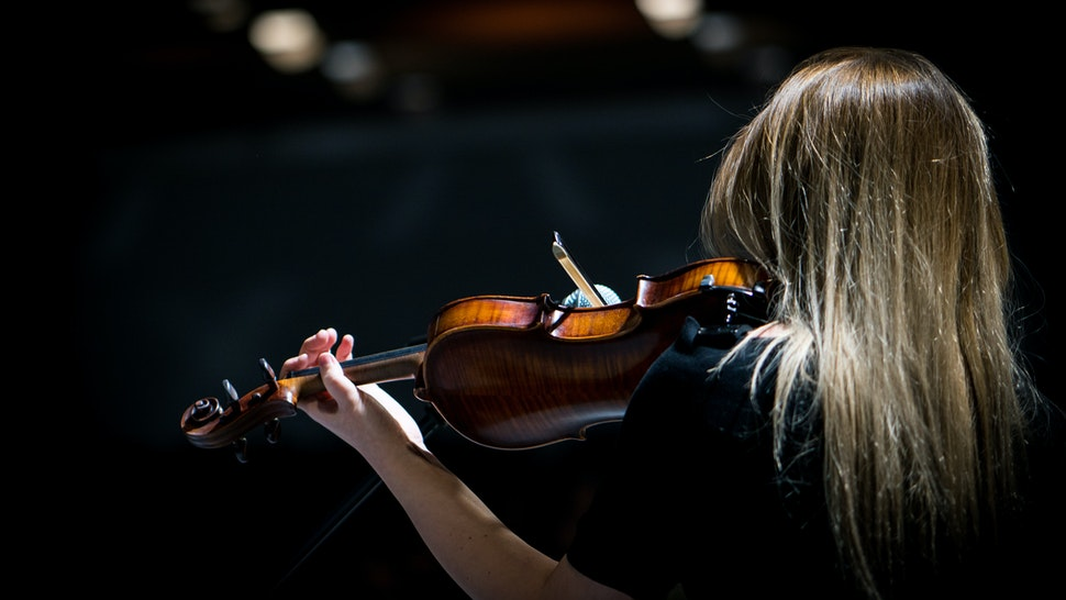 Beautiful girl playing the violin in concert hall