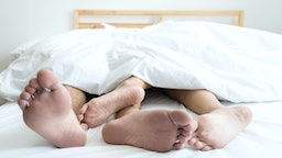 Low Section Of Couple Sleeping On Bed At Home - stock photo
