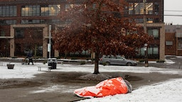 A homeless man, who said he was aware of the forecast for extreme weather, rests in a park while covered with snow on February 8, 2019 in Seattle, Washington.