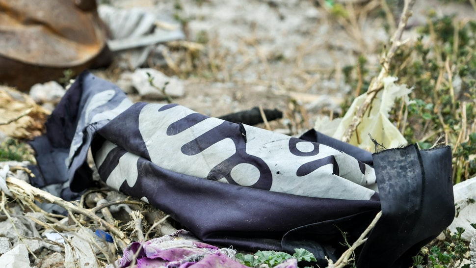 """This picture taken on March 24, 2019 shows a discarded Islamic State (IS) group flag lying on the ground in the village of Baghouz in Syria's eastern Deir Ezzor province near the Iraqi border, a day after IS group's """"caliphate"""" was declared defeated by the US-backed Kurdish-led Syrian Democratic Forces (SDF). (Photo by GIUSEPPE CACACE / AFP) (Photo credit should read GIUSEPPE CACACE/AFP/Getty Images)"""