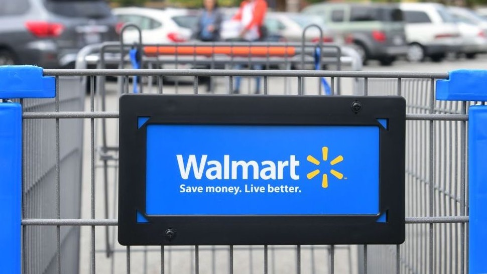 Shoppers carry their goods past a shopping cart in the parking lot of a Walmart Supercenter in Rosemead, California on May 23, 2019. - Walmart has said it will raise prices as a result of the Trump administration's tariffs on Chinese-made goods as the trade war is about to take a bite into the retail sector affecting consumers shopping at stores like Walmart, Target and Macy's.