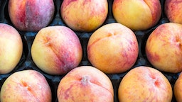 Large peaches forming a pattern inside of a box. Peaches are a healthy food because they are rich in potassium plus vitamins A, C, and E.