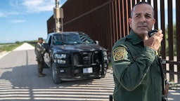 U.S. Border Patrol agent Carlos Ruiz spots a pair of undocumented immigrants while coordinating with active duty U.S. Army soldiers near the U.S.-Mexico border fence on September 10, 2019 in Penitas, Texas.