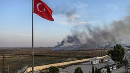 Smoke rises from the Syrian town of Tal Abyad, in a picture taken from the Turkish side of the border where the Turkish flag is seen in Akcakale on October 10, 2019, on the second day of Turkey's military operation against Kurdish forces.