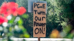 A sign calling for utility company PG&E to turn the power back on is seen on the side of the road during a statewide blackout in Calistoga, California, on October, 10, 2019