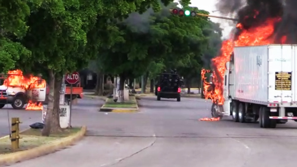 """In this AFPTV screen trucks burn in a street of Culiacan, capital of jailed kingpin Joaquin """"El Chapo"""" Guzman's home state of Sinaloa, on October 17, 2019. - Heavily armed gunmen in four-by-four trucks fought an intense battle against Mexican security forces Thursday in the city of Culiacan, capital of jailed kingpin Joaquin """"El Chapo"""" Guzman's home state of Sinaloa."""
