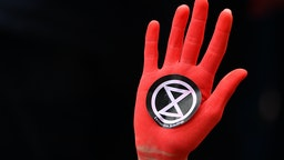 A protesters hand sprayed red in Westminster, London, during an Extinction Rebellion (XR) climate change protest. (Photo by Dominic Lipinski/PA Images via Getty Images)