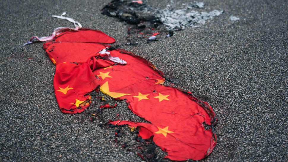 """A Chinese national flag burnt on a street on October 01, 2019 in Hong Kong, China. Pro-democracy protesters marked the 70th anniversary of the founding of the People's Republic of China in Hong Kong through demonstrations as the city remains on the edge with the anti-government movement entering its fourth month. Protesters in Hong Kong continued their call for Chief Executive Carrie Lam to meet their remaining demands since the controversial extradition bill has been withdrawn, which includes an independent inquiry into police brutality, the retraction of the word """"riot"""" to describe the rallies, and genuine universal suffrage, as the territory faces a leadership crisis."""