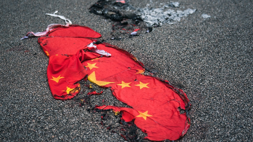 "A Chinese national flag burnt on a street on October 01, 2019 in Hong Kong, China. Pro-democracy protesters marked the 70th anniversary of the founding of the People's Republic of China in Hong Kong through demonstrations as the city remains on the edge with the anti-government movement entering its fourth month. Protesters in Hong Kong continued their call for Chief Executive Carrie Lam to meet their remaining demands since the controversial extradition bill has been withdrawn, which includes an independent inquiry into police brutality, the retraction of the word ""riot"" to describe the rallies, and genuine universal suffrage, as the territory faces a leadership crisis."