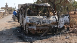 27 October 2019, Syria, Barisha: Syrians inspect a burnt vehicle at the site near the northwestern Syrian village of Barisha in the province of Idlib near the border with Turkey, after media reports said Islamic State (IS) leader Abu Bakr al-Baghdadi was believed to be killed in a US Special Forces raid in the same province. Photo: Mustafa Dahnon/dpa (Photo by Mustafa Dahnon/picture alliance via Getty Images)