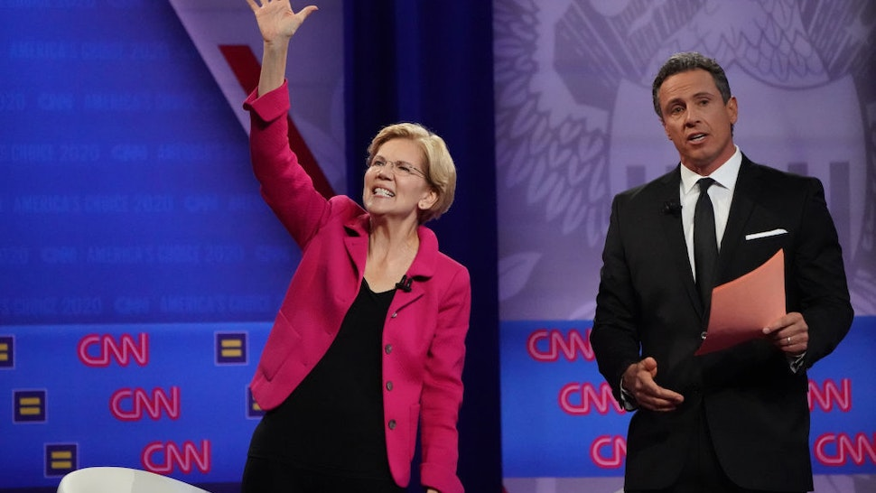 Democratic presidential candidate Sen. Elizabeth Warren (D-MA), L, waves as CNN moderator Chris Cuomo looks on at the Human Rights Campaign Foundation and CNN's presidential town hall focused on LGBTQ issues on October 10, 2019 in Los Angeles, California.