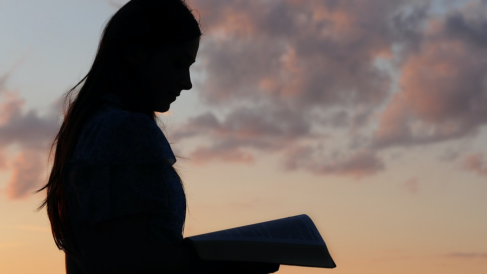 Silhouette of a young girl reading from Bible in sunset light.
