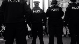 Rear View Of Police Force Standing On Street Against Buildings In City - stock photo