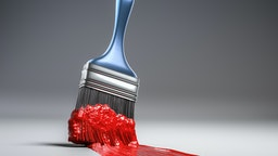 A blue handled paint brush sweeps across a white background with thick red paint