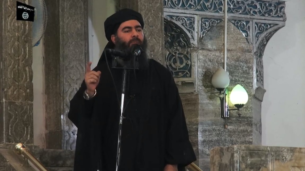"This July 5, 2014 photo shows an image grab taken from a propaganda video released by al-Furqan Media allegedly showing the leader of the Islamic State (IS) jihadist group, Abu Bakr al-Baghdadi, aka Caliph Ibrahim, adressing Muslim worshippers at a mosque in the militant-held northern Iraqi city of Mosul. Baghdadi, who on June 29 proclaimed a ""caliphate"" straddling Syria and Iraq, purportedly ordered all Muslims to obey him in the video released on social media. - In early 2014 the self-styled Islamic State entered the northern Syrian city of Raqqa, declaring it their capital and beginning a reign of terror marked by grisly public executions. Armed sharia police patrolled the streets as ""enemies"" of the regime were crucified or decapitated, their severed heads impaled on spikes in the city square. (Photo by - / AFP) (Photo by -/AFP via Getty Images)"