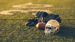 A Gold American Football helmet sits with a football on a football playing field. The light is from the sun which is about to set, shallow depth of field. Copy space included. Sport background image.