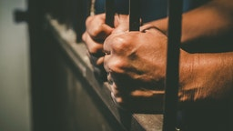 hands holding on to prison bars