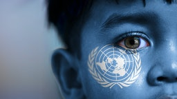 Boy's face, looking at camera, cropped view with digitally placed United Nations flag on his face.