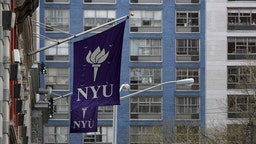 New York University banners hang from a building in New York, U.S., on Monday, April 5, 2010. New York University will face financial hurdles and a fight with Greenwich Village preservationists as it tries to take over more space and compete harder with uptown rival Columbia University.