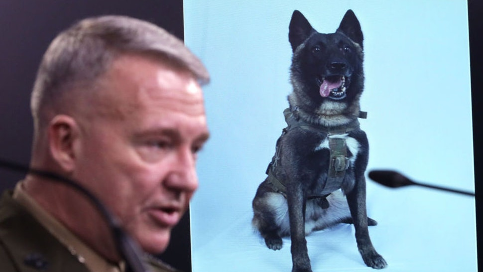 ARLINGTON, VIRGINIA - OCTOBER 30: U.S. Marine Corps Gen. Kenneth McKenzie, commander of U.S. Central Command, speaks as a picture of the canine that was part of the operation, is on display during a press briefing October 30, 2019 at the Pentagon in Arlington, Virginia. Gen. McKenzie and Hoffman spoke to the media to provide an update on the special operations raid that targeted former ISIS leader Abu Bakr al-Baghdadi in Idlib Province, Syria.