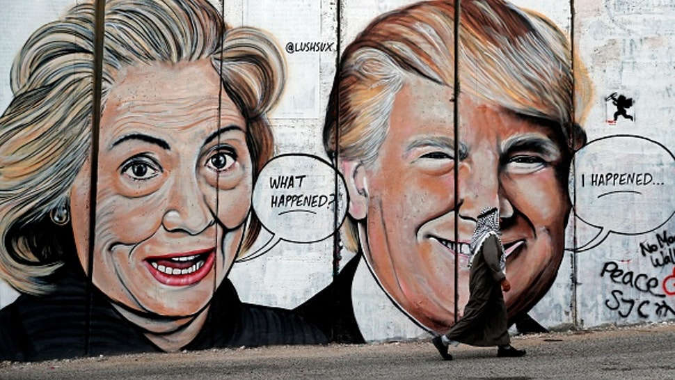 TOPSHOT - A Palestinian man walks past a newly sprayed graffiti depicting US presidential candidate Hillary Clinton and US President Donald Trump on the controversial Israeli separation wall separating the West Bank town of Bethlehem from Jerusalem on October 30, 2017.