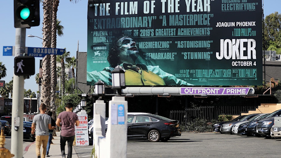 WEST HOLLYWOOD, CALIFORNIA - OCTOBER 03: People walk past a billboard displayed for the new film 'Joker' on October 3, 2019 in West Hollywood, California. Security measures have been tightened in some cities around the film's opening weekend following concerns of potential violence at theaters.