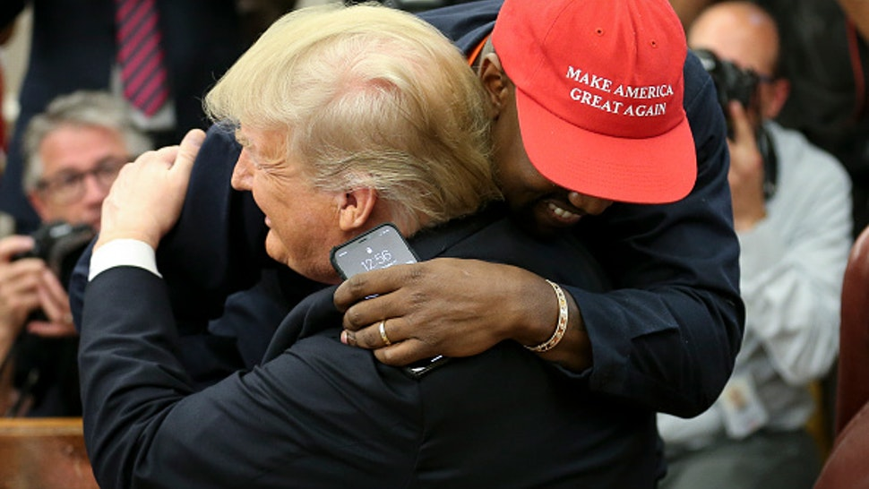 WASHINGTON, DC - OCTOBER 11: (AFP OUT) (EDITORS NOTE: Retransmission with alternate crop.) U.S. President Donald Trump hugs rapper Kanye West during a meeting in the Oval office of the White House on October 11, 2018 in Washington, DC.