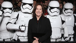 """HOLLYWOOD, CA - DECEMBER 14: Lucasfilm President Kathleen Kennedy poses with Stormtroopers at the Premiere of Walt Disney Pictures and Lucasfilm's """"Star Wars: The Force Awakens"""" at on December 14, 2015 in Hollywood, California."""