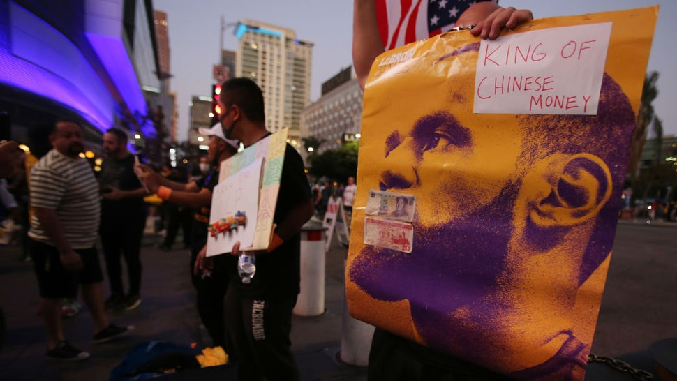 A pro-Hong Kong activist holds a poster of LeBron James with the words 'King of Chinese Money' before the Los Angeles Lakers season opening game against the LA Clippers outside Staples Center on October 22, 2019 in Los Angeles, California. Activists also printed at least 10,000 pro-Hong Kong t-shirts to hand out to those attending the game and encouraged them to wear the free shirts as a form of peaceful protest against China amidst Chinese censorship of NBA games. (Photo by Mario Tama/Getty Images)
