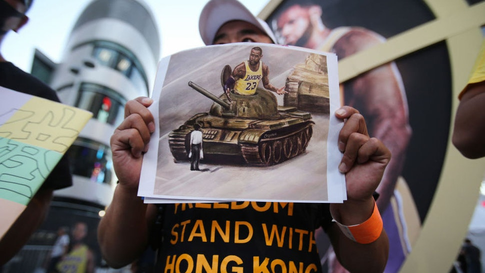 A pro-Hong Kong activist holds an image depicting LeBron James aboard a Chinese tank in Tiananmen Square before the Los Angeles Lakers season opening game against the LA Clippers outside Staples Center on October 22, 2019 in Los Angeles, California. Activists also printed at least 10,000 pro-Hong Kong t-shirts to hand out to those attending the game and encouraged them to wear the free shirts as a form of peaceful protest against China amidst Chinese censorship of NBA games. (Photo by Mario Tama/Getty Images)