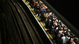 Commuters wait for a train on a Central Line platform at Stratford station in east London. (Photo by Victoria Jones/PA Images via Getty Images)