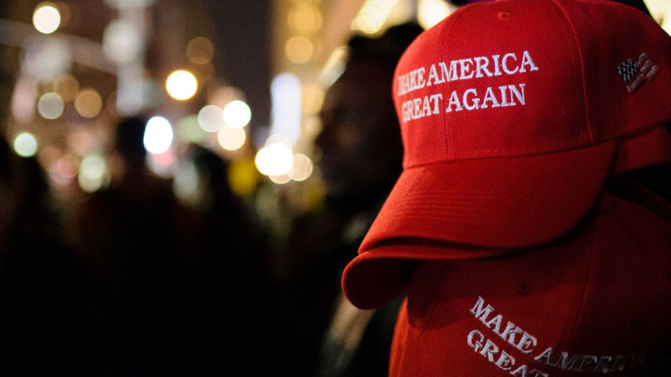 """Make America Great Again"" red baseball caps, signature headwear of the Donald Trump campaign and its supporters, stand on sale on 6th Avenue in Midtown Manhattan in the second hour after Election Day as election results point to a shock Trump win. (Photo by David Cliff/SOPA Images/LightRocket via Getty Images)"